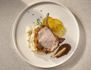 Carré de porc du Québec sous croûte au vieux cheddar et au sucre d'érable, purée d'ail noir à l'érable